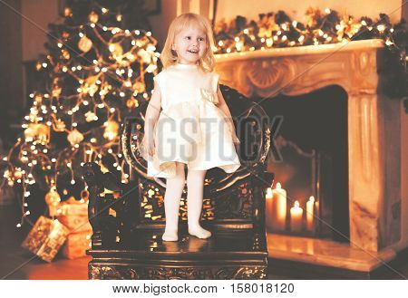 Christmas Happy Child Little Girl Over Christmas Tree Bokeh And Fireplace At Home