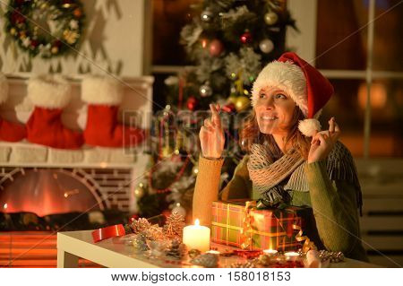 Portrait of smiling woman with Christmas gift ar home  keeps fingers crossed