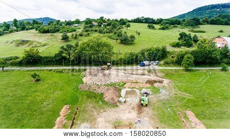 Construction site. Building concrete foundation for a new house. Pouring wet cement in. Concrete mixer truck. Cement transportation machine. Beautiful summer nature.