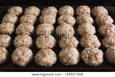 Lots uncooked meatballs on the dark tray
