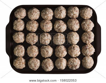 Lots uncooked meatballs on the dark tray isolated