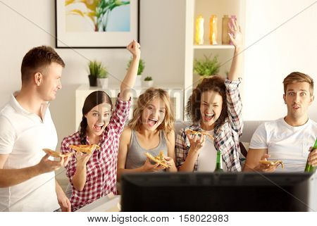 Friends eating pizza and watching TV at home party