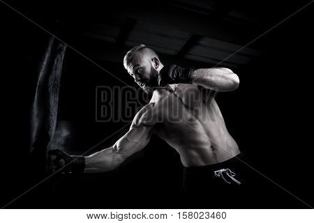 Male Athlete Boxer Punching A Punching Bag With Dramatic Edgy Lighty In A Dark Studio