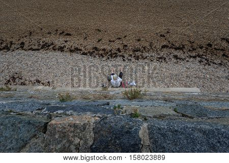 Woman resting on the beach below high wall