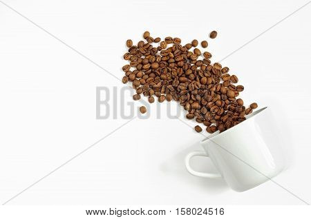 Spilled Coffee Beans From The White Ceramic Cup