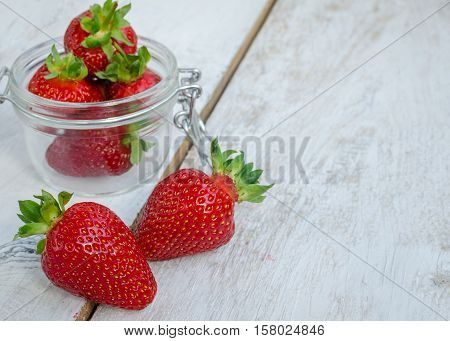 Red berry strawberry in glass jar on white rustic wooden background. Background from freshly harvested strawberries. Strawberry background. Selective focus. Shallow depth of field. Horizontal.