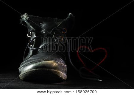 Old worn out black shoe in love forms a blushing red heart with its shoelace against a dark background concept for late love in old age fidelity or a special greeting card for valentine's day selective focus