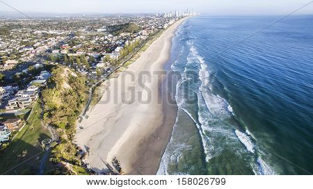 Aerial view of Miami Headland and beach as the sunrise glow hits the foreshore. Gold Coast, Australia