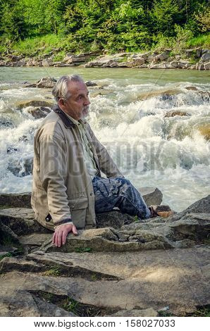 Senior man is sitting and thinking near the waterfall in the beautiful place. Looking far away. Serious senior man with gray hair and beard. Vertical image.
