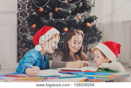 Writing letter to santa. Adorable children in santa hats make wish list of presents for christmas. Waiting for gift. Prepare for winter holidays. Boys and girl, brothers and sister in decorated room