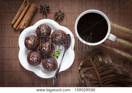 Sweet chocolate cake pop in wood background.Homemade delicious chocolate cake ball.Black coffee cup with sweet cake.