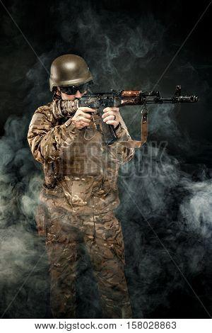 Studio shot of serviceman wearing military uniform standing in smoke and aiming with gun.