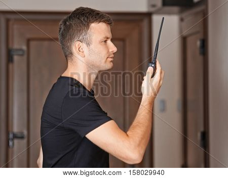 Security man standing indoors and using portable radio