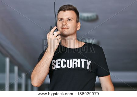 Security man in corridor using portable radio