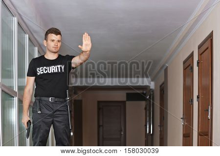 Security man showing stop sign with hand