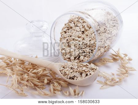 Oat flakes in a bowl of glass and ears of oats on a white background close.