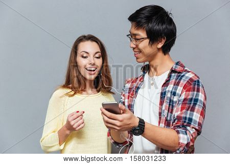 Happy multicultural couple listening to music with the same pair of earphones isolated on the gray background