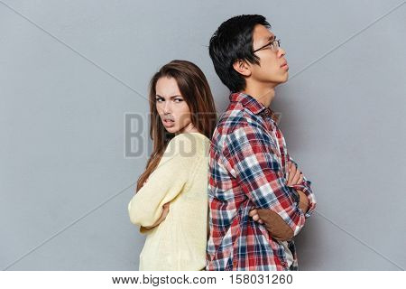 Unhappy young couple standing with arms crossed isolated on the gray background