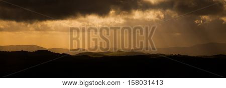 Dramatic panorama. sun beams bursting through dark stormy clouds. Czech Central Mountainc, aka Ceske Stredohori, Czech Republic