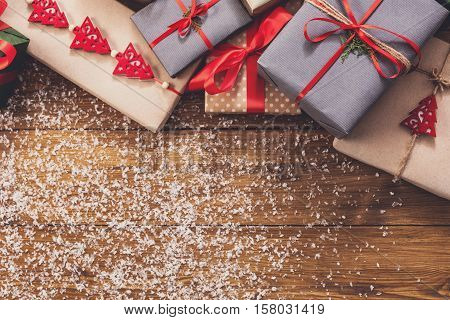Christmas decoration, gift boxes and garland frame concept background, top view with copy space on wood table surface. Christmas ornaments and presents border with snow