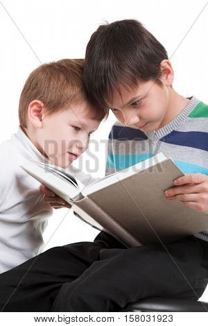 Two happy boys reading big book solated on white background