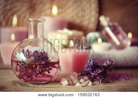 Spa concept. Bottle with lavender aroma oil and candles on wooden background