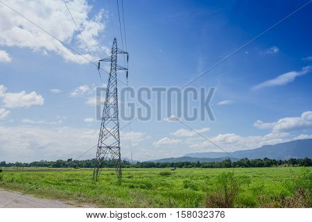 Electric post in farmland with the blue sky High voltage transmission tower