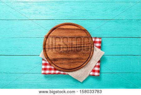 Round cutting board on red plaid and gray tablecloth. Top view