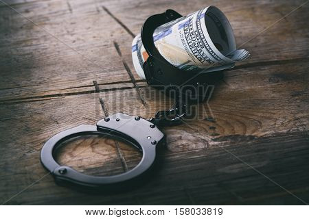 Handcuffs With Money On Wooden Background