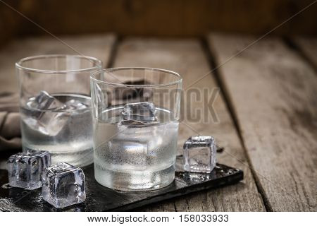 Vodka in shot glasses on rustic wood backgroundcopy space
