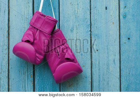 Pink boxing gloves on blue cracked wooden background empty space on the right