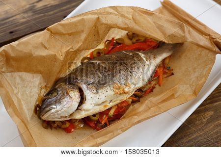 Baked in a parchment sleeve fish with a vegetable garnish of tomato, green pepper, onion, carrots and zucchini on a plate on a wooden table