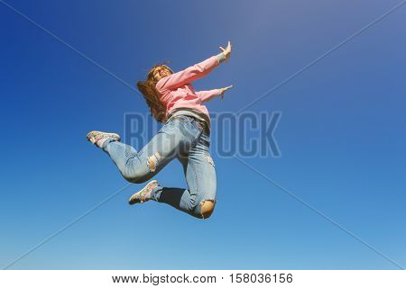 Young beautiful woman dancer jumping on a background of blue sky