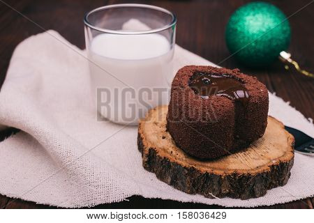 Close-up of chocolate cake glass of milk and Christmas ball on a wooden table