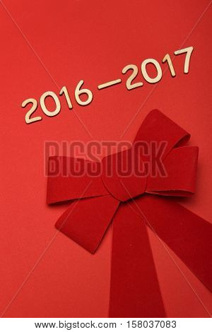 Wooden 2016 - 2017. New year text on plank wood. Red velvet bow