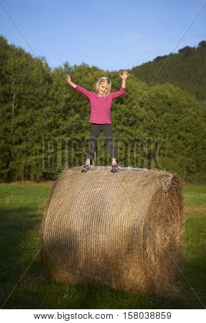 Child blond Girl by straw hay bale in field, meadow, playing, children summer activities