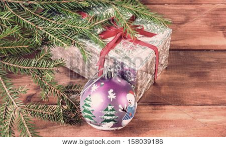 Wrapped in shiny paper gift box under the tree. Image in vintage style
