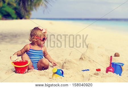 cute little girl playing with sand on tropical beach, family beach vacation