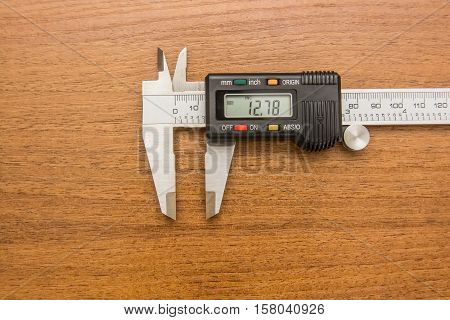 Close-up photography of engineering caliper on wooden background