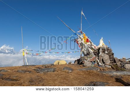 Camping Tent On The Top Of The Pikey Peak Mountain Next To Buddhist Chorten And Waving Prayer Flags.