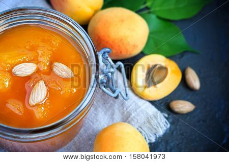 Fresh apricot jam in jar and ripe apricots closeup