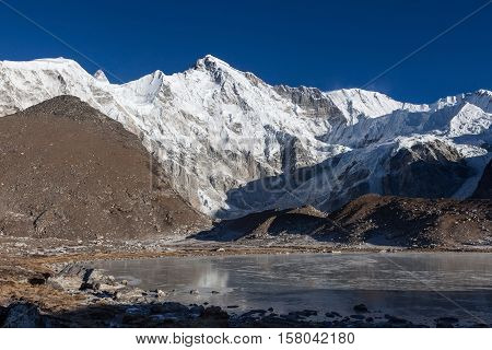 Beautiful Mountain Cho Oyu And Gray Moraine Lake Covered With Ice. Beautiful Mountain Landscape Saga