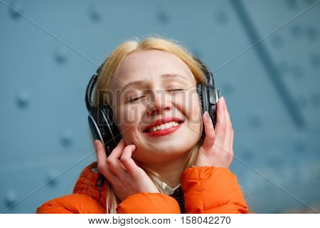 Girl with closed eyes listening to music in blue wall