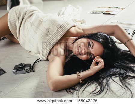 Curvy sexy young brunette woman lying on floor among the glamorous magazines and retro camera. Studio shot, warm toning picture.