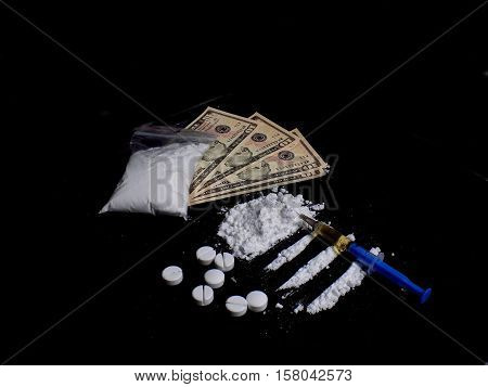 Injection syringe on cocaine drug powder lines and pile, pills and cocaine bag on dollar bills money on black background