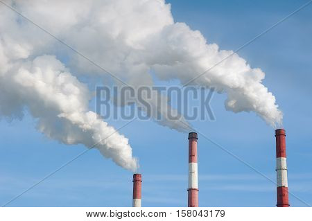 Air pollution by smoke coming out of the three factory chimneys.