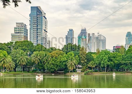 Bangkok, Thailand - December 23, 2015: People relax on a boat in a city park. Pleasureboats on a lake in the heart of Bangkok - Lumphini Park.