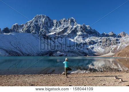 Young Woman Practicing Yoga Tree Pose (vriksasana) On The Shore Of Turquoise Gokyo Lake Under Snowy