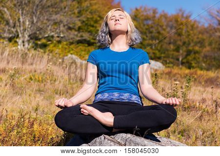 Young woman meditating sitting on rock cross legged in field in yoga pose