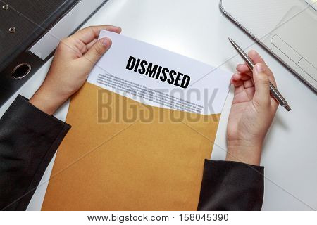 Businesswoman opening Dismissed document in letter envelope